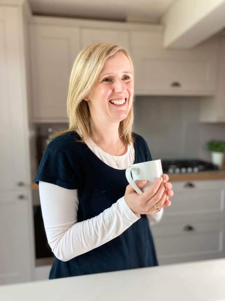 Claire Carter Profile standing in kitchen holding mug