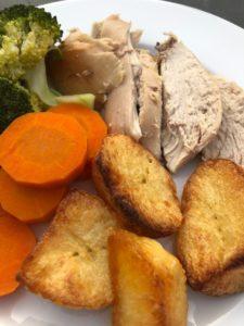 roast chicken roast potatoes carrots and broccoli on plate