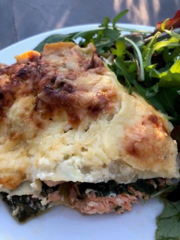 salmon and spinach lasagna plated with green salad