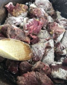 diced beef and flour frying in pan