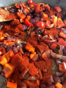 red onions red pepper and paprika in pan