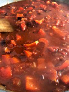 spicy bean goulash simmering in pan