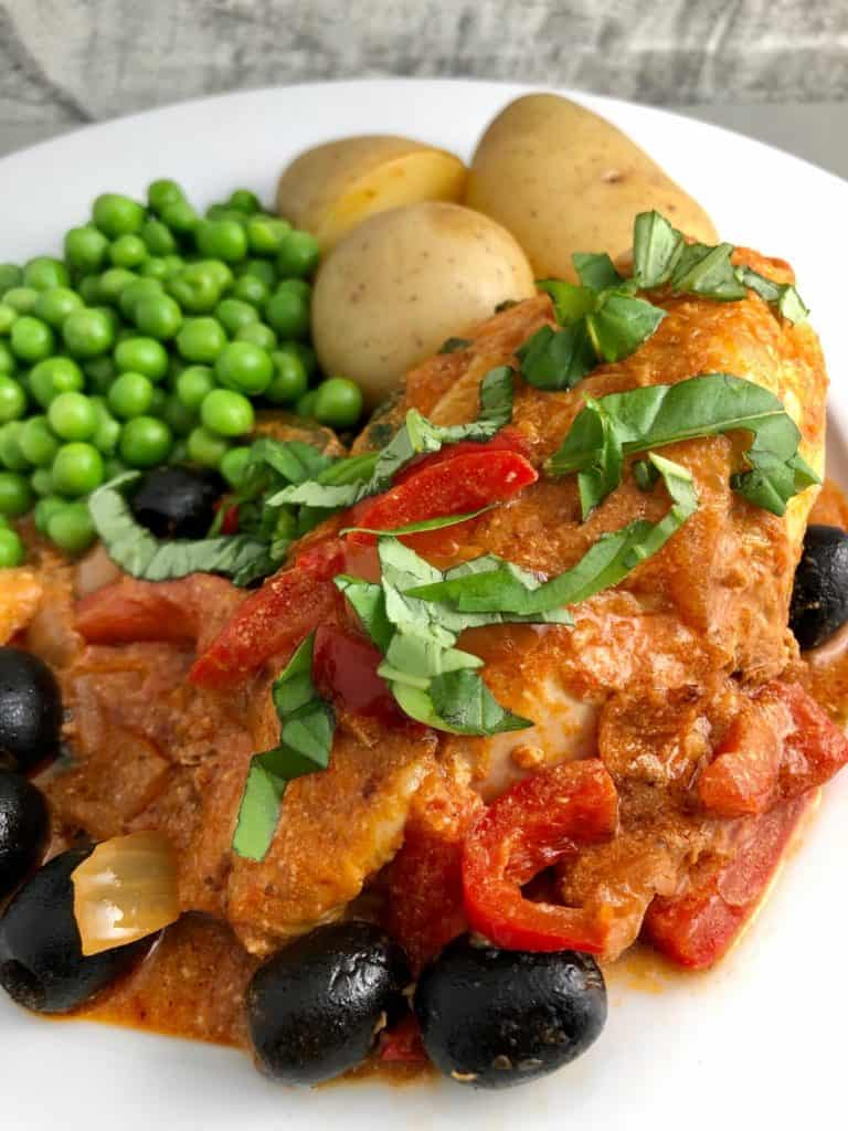 Chicken red pesto olives on plate new potatoes peas