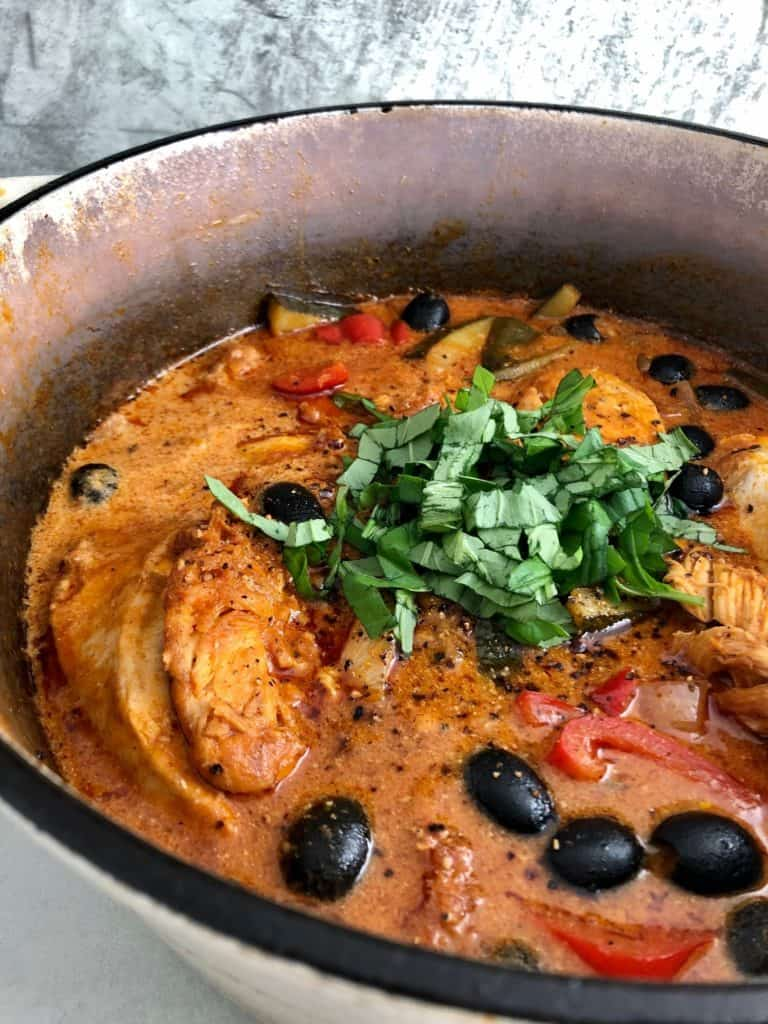 chicken red pesto and olives in pan with fresh basil