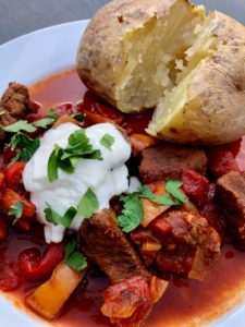 hungarian beef goulash with jacket potato and soured cream