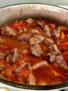hungarian beef goulash simmering in pan
