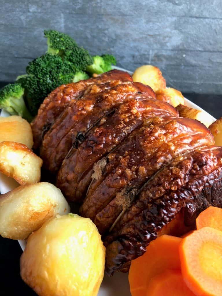 Roast Pork Loin joint roast potatoes carrots broccoli on plate
