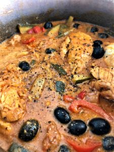 Chicken with red pesto and olives in pan