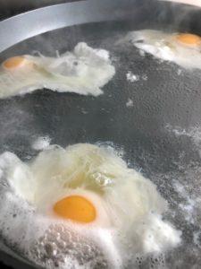 4 eggs poaching in pan