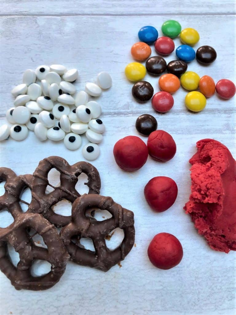 Gingerbread biscuit decorations pretzels candy eyes m&m's red icing