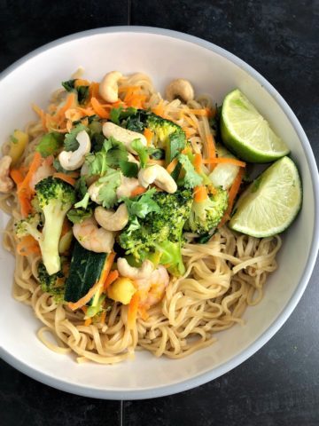 Stir fry Prawns with noodles cashew nuts sliced lime in bowl