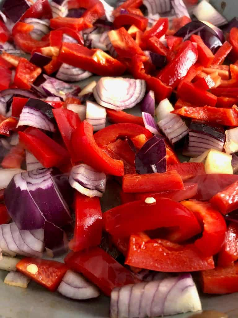 red onions and peppers frying in pan