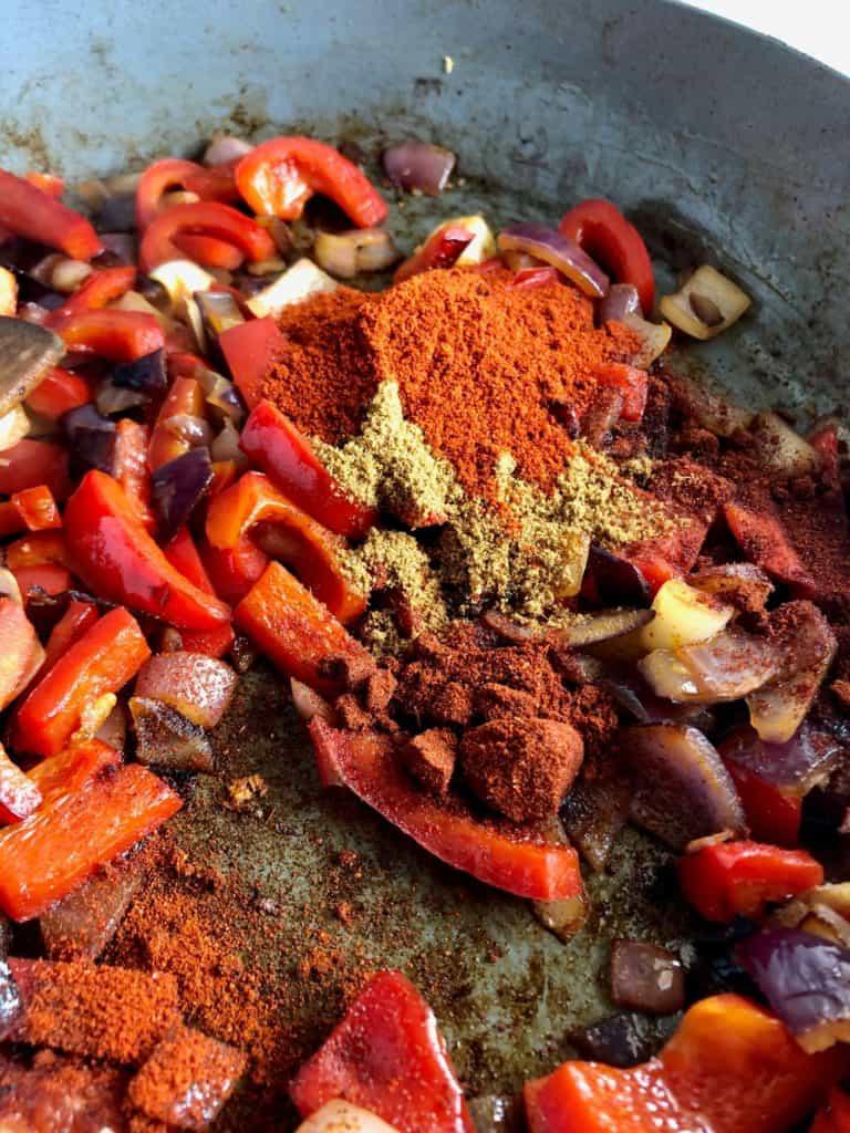 fried onion red pepper chilli powder paprika cumin in pan