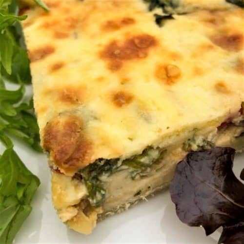 slice quiche on plate with salad