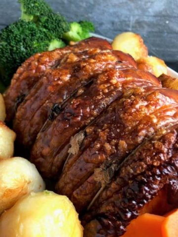 roast pork joint with roast potatoes carrots and broccoli
