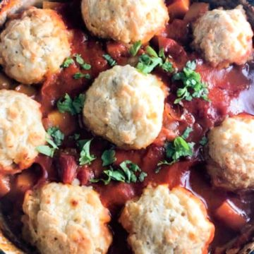 winter vegetable stew in tomato sauce with cheesy dumplings