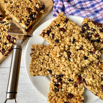 Oat Flapjacks with dried fruit cut up on plate and chopping board