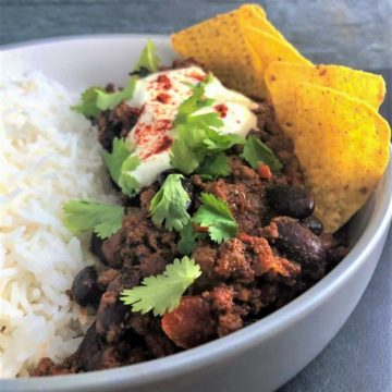 Chilli in a bowl with rice and tortilla chips
