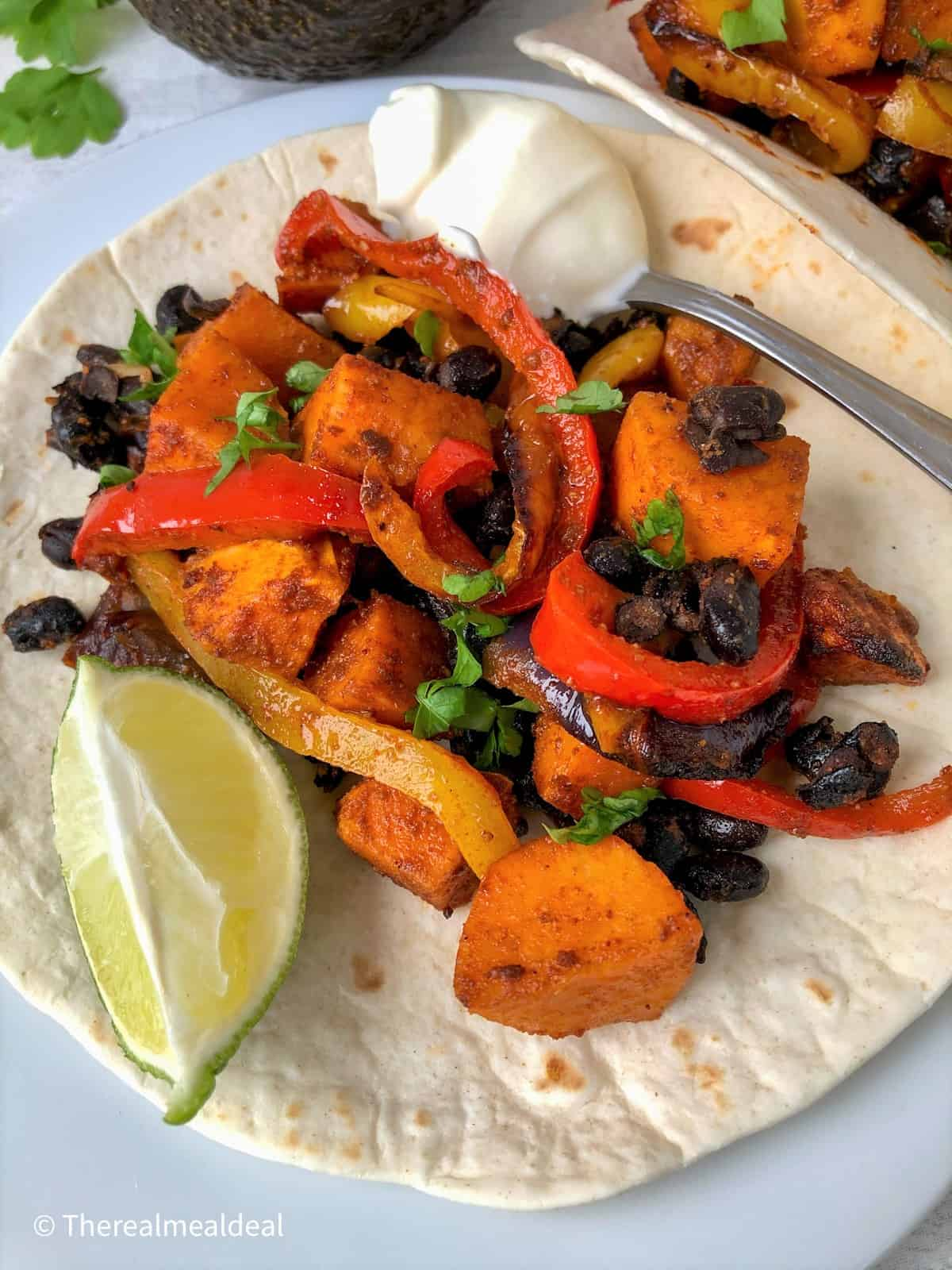 roasted vegetables on open tortilla with slice lime and spoonful soured cream