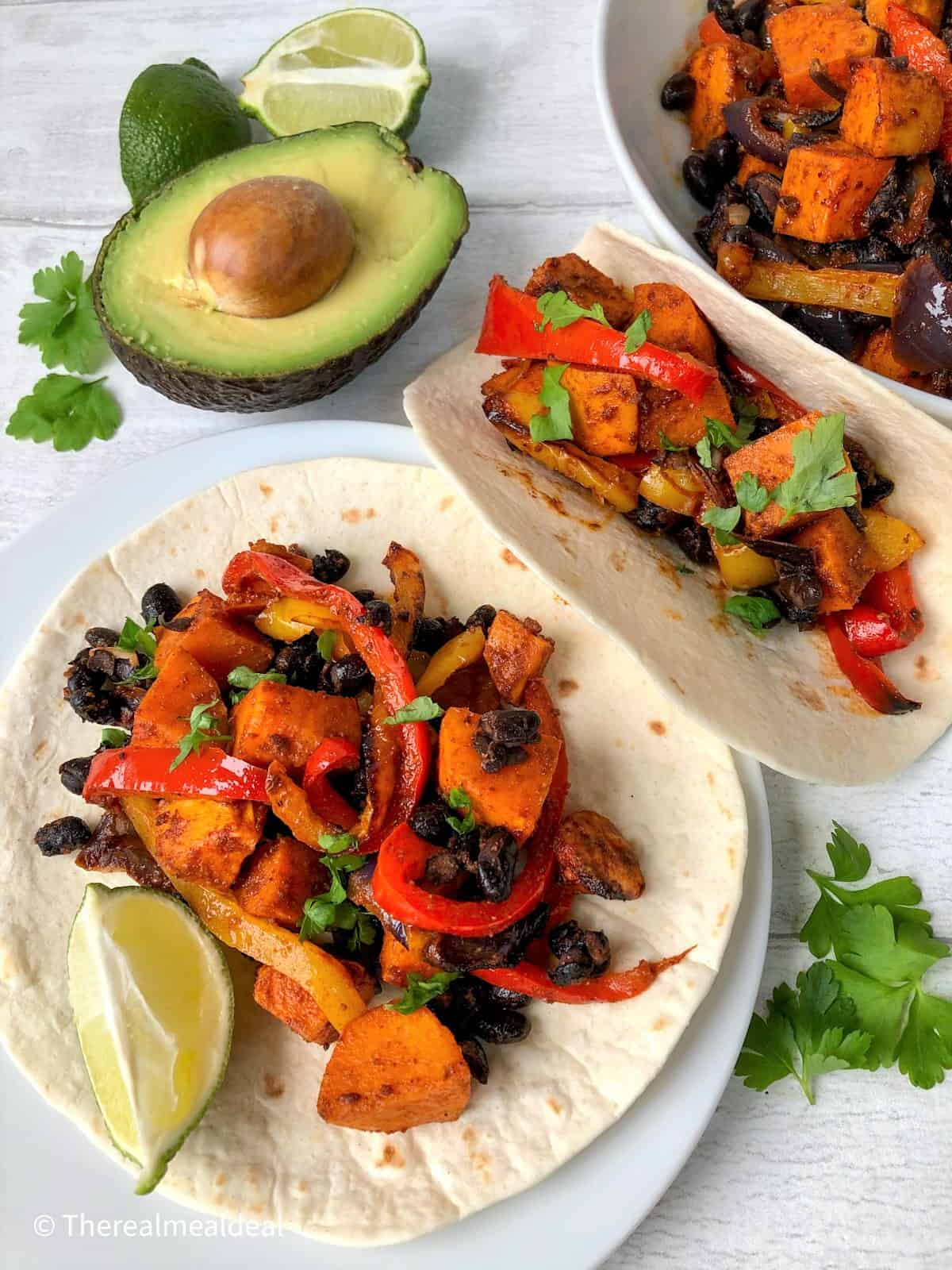 roasted vegetables on open tortillas served with avocado and slice lime