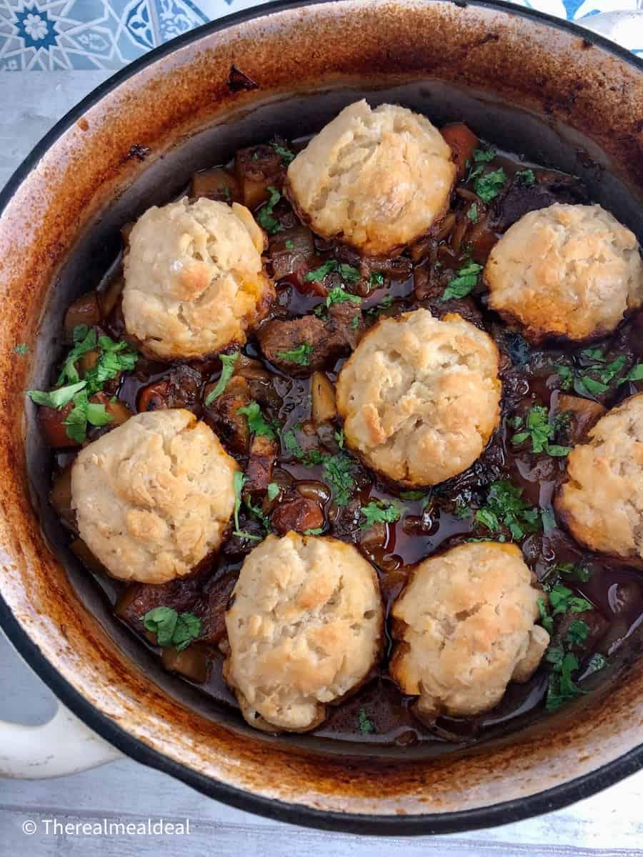 beed stew in casserole pot with 8 dumplings on top