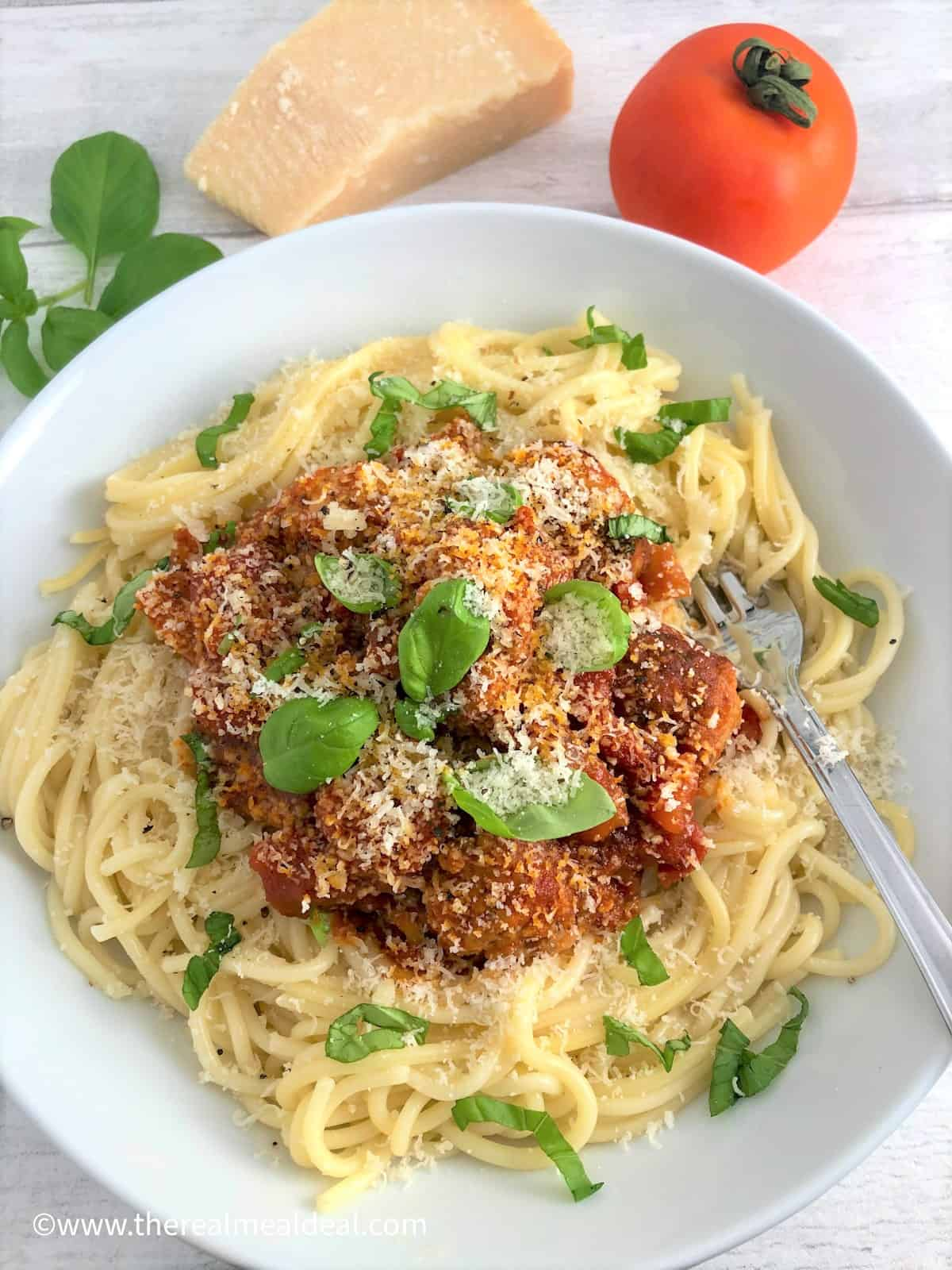 pork meatballs in a tomato sauce on top of spaghetti topped with parmesan cheese and fresh basil