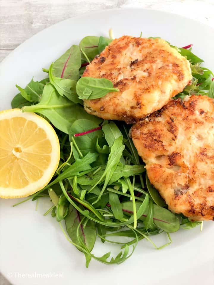 Fried salmon fishcakes served with green salad and lemon half