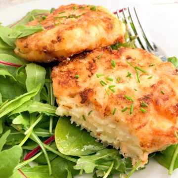 salmon fishcakes showing inside of mash, flaked fish and chives