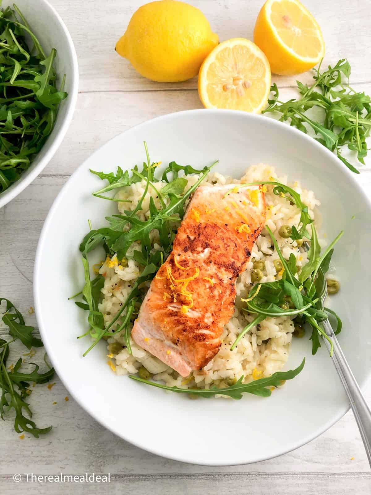 pan fried salmon fillet on risotto topped with rocket leaves