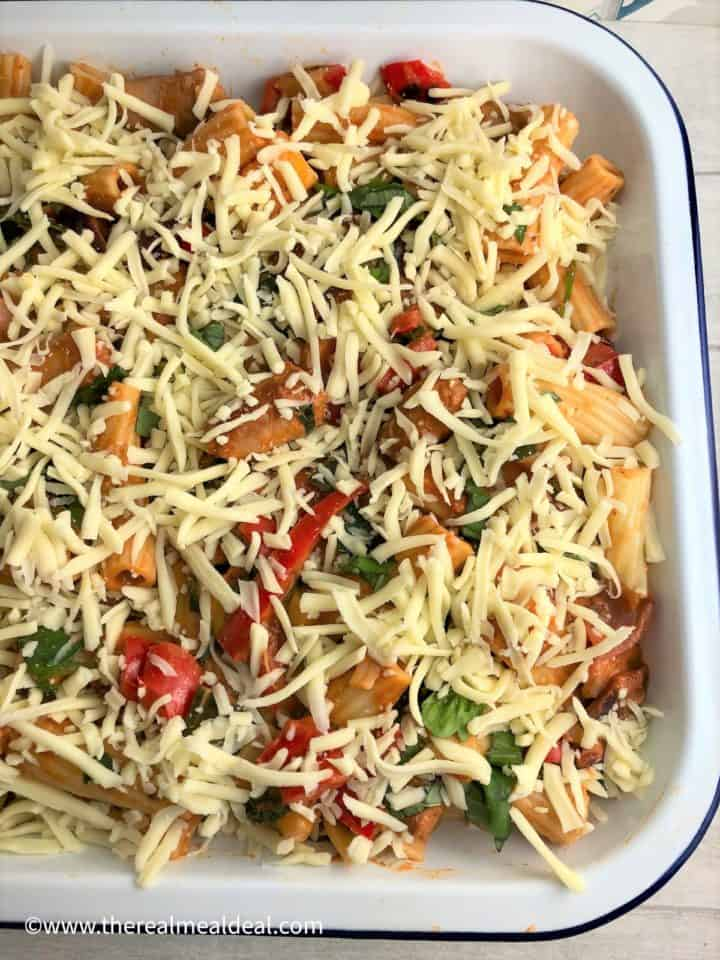 sausage pasta bake with grated mozarella ready for oven