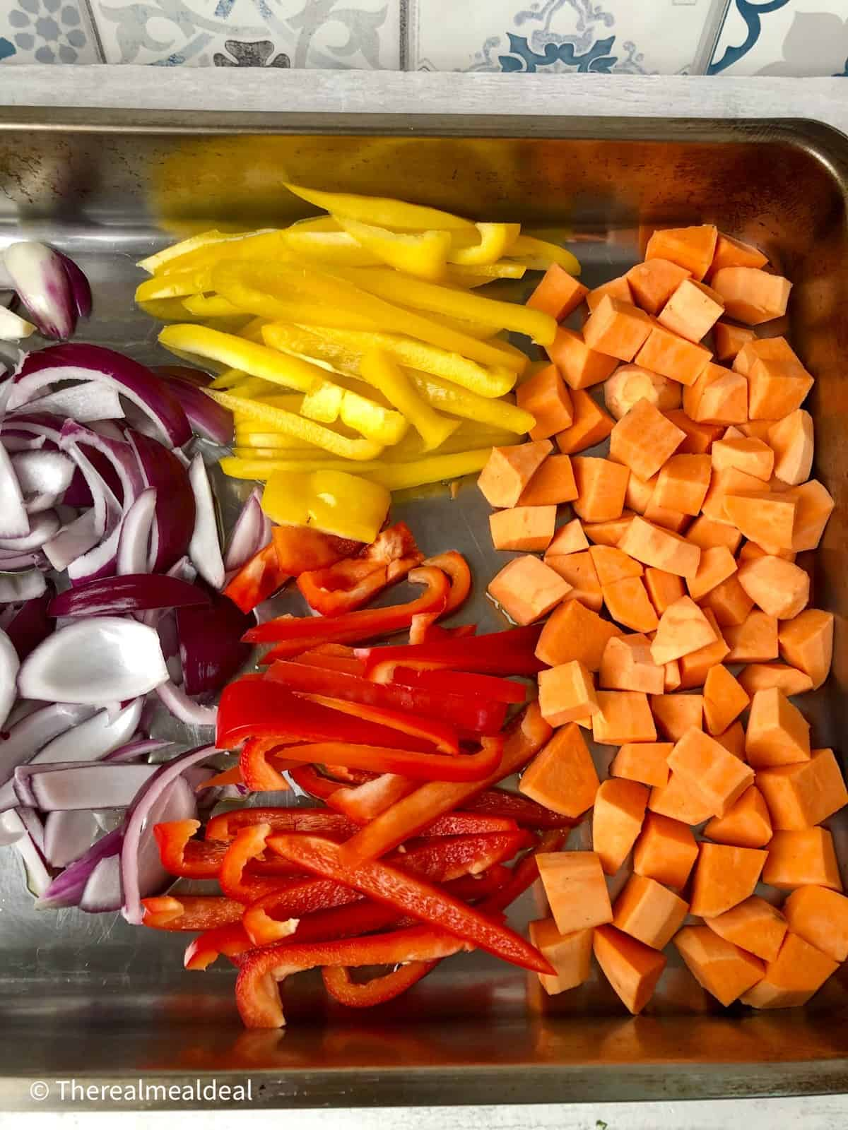 sliced peppers red onion and diced sweet potatoes in roasting tin