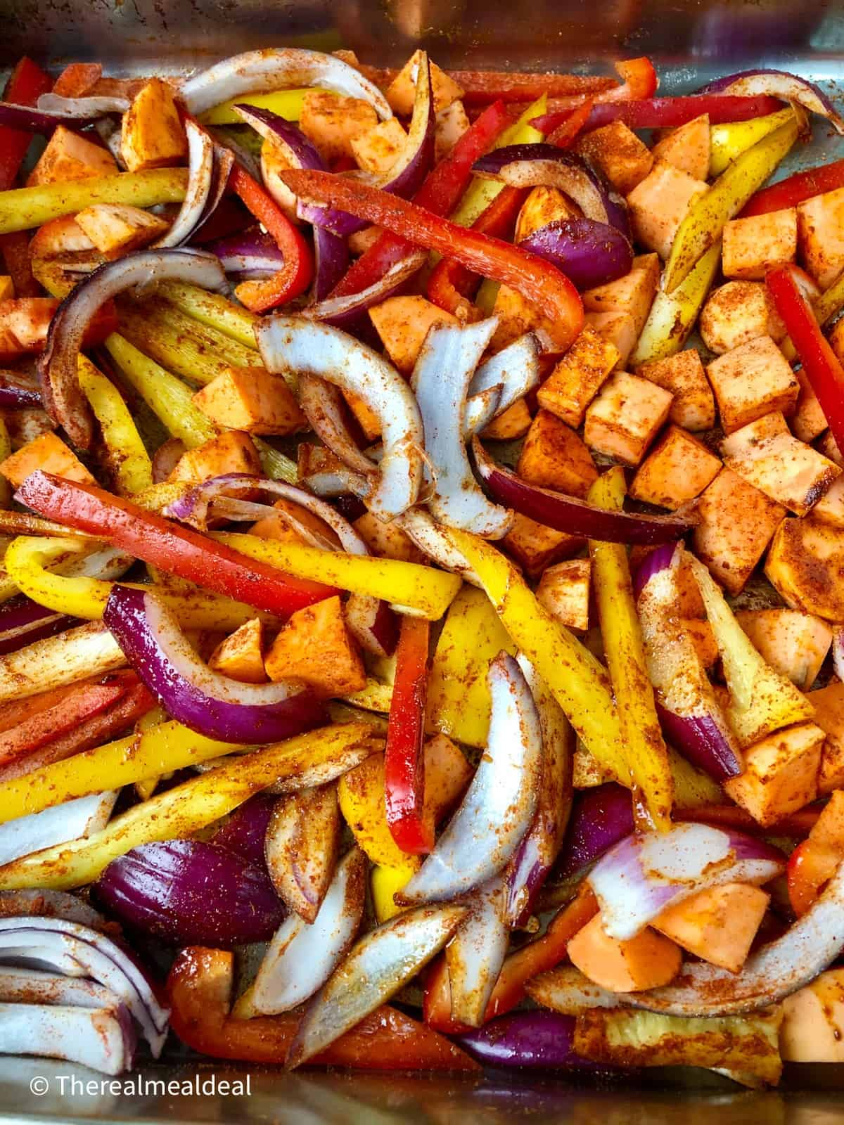 sliced red and yellow peppers red onion diced sweet potato coated in spice mix in roasting tray