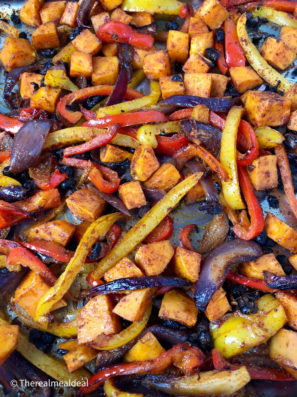 Roasted red and yellow peppers red onions sweet potatoes and black beans in a tray