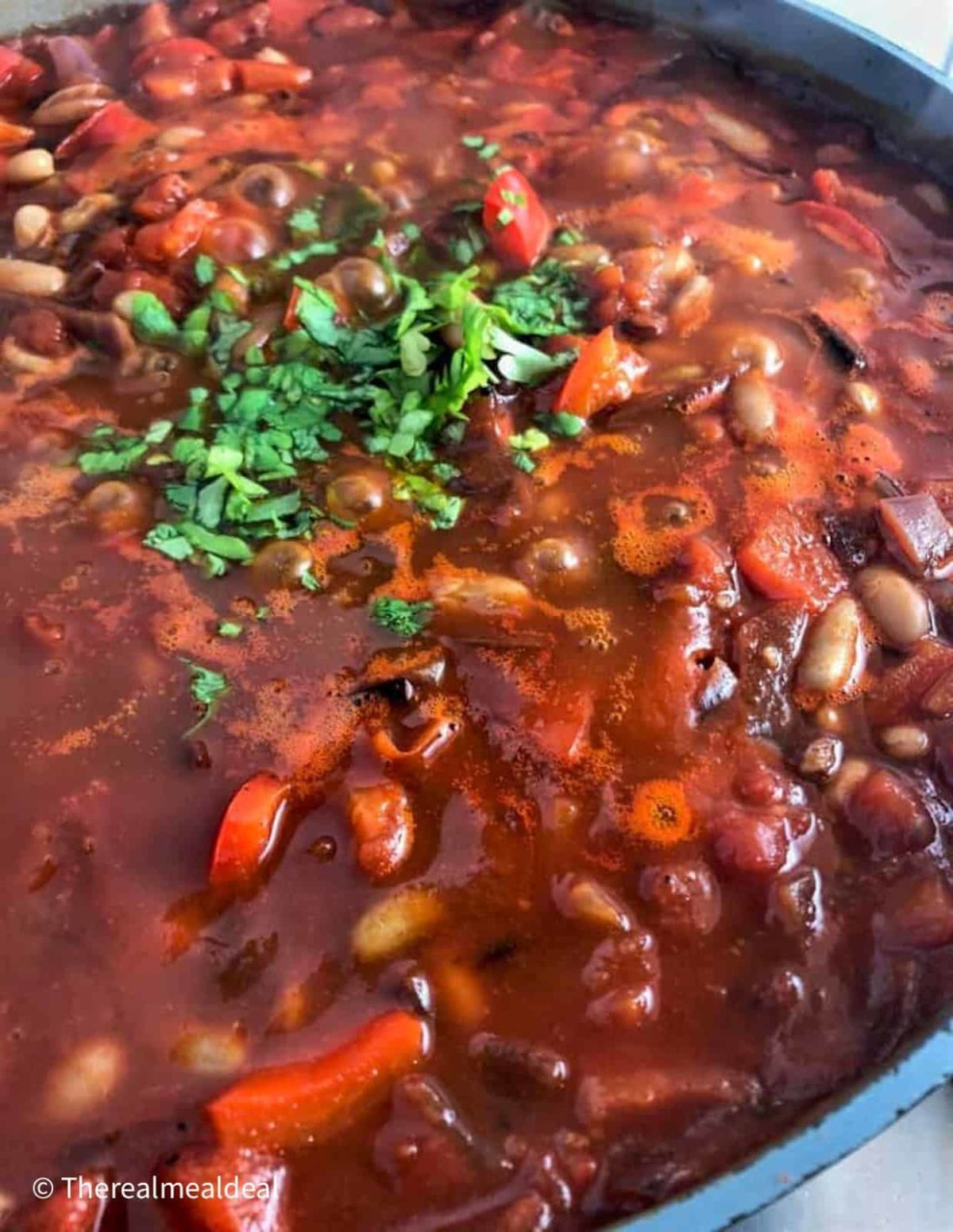 Vegetarian goulash simmering in a pan with fresh parsley added