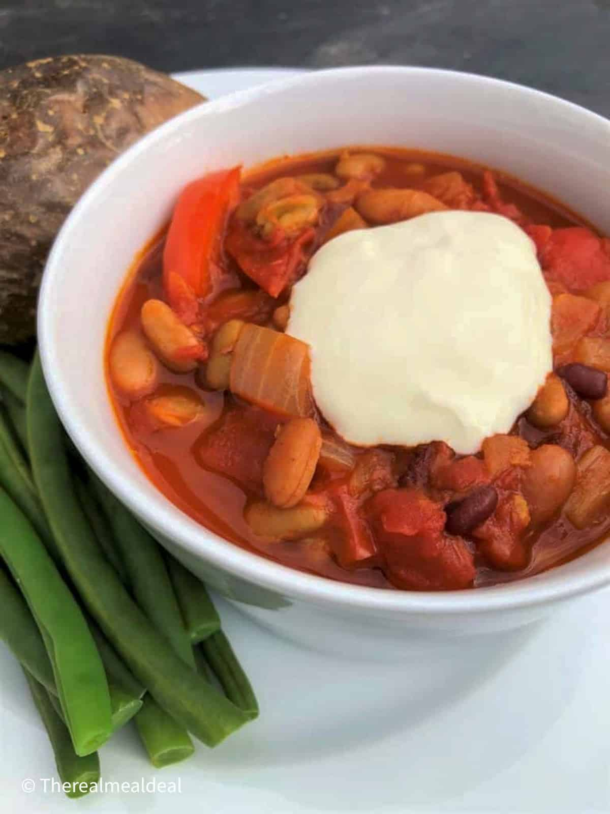 bowl of vegetarian goulash with soured cream jacket potato and green beans on the side