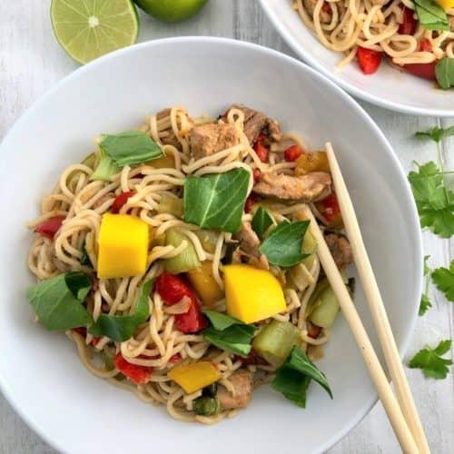 pork stir fry in bowl with chopsticks cut lime to side
