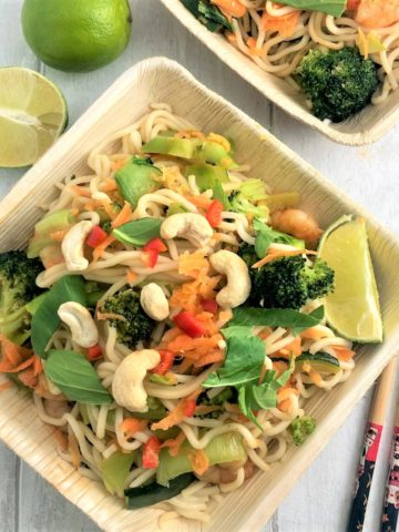 prawn stir fry with noodles topped with cashew nuts in bamboo bowl with chopsticks to side and sliced lime
