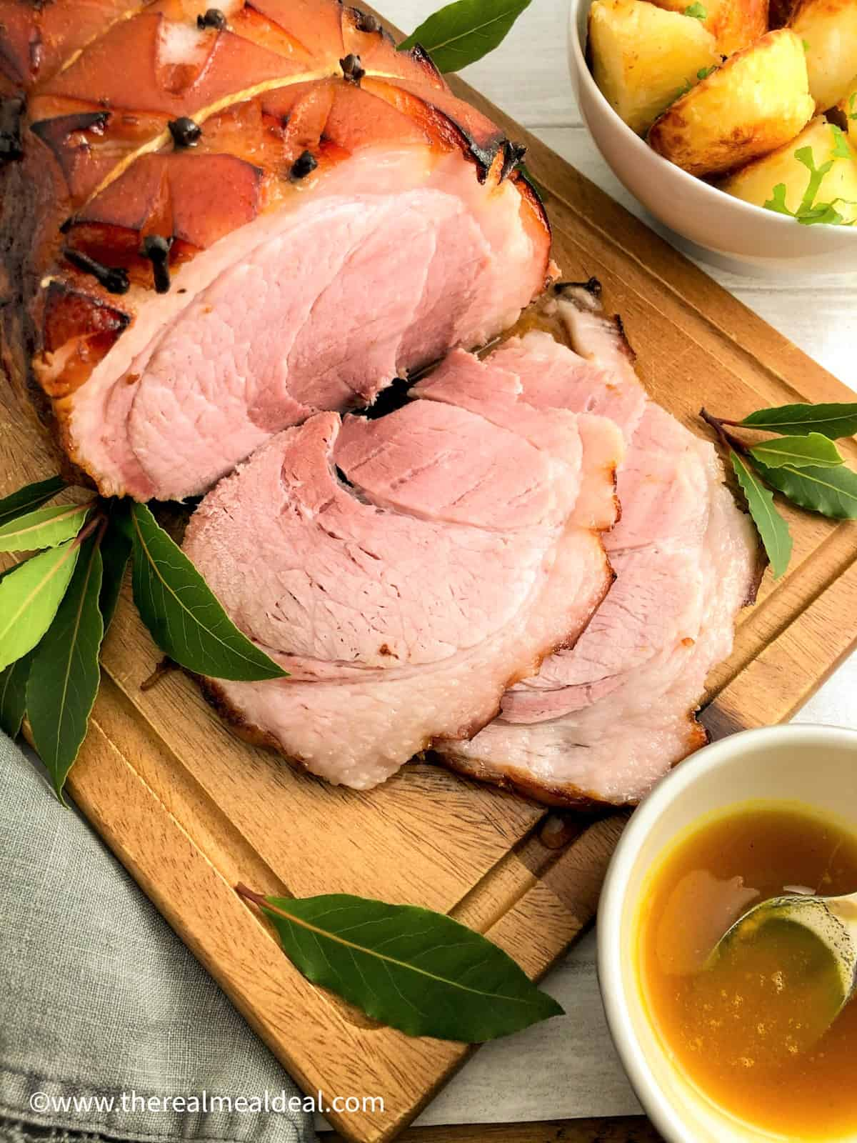 honey roast gammon on board sliced wiht bay leaves roast potatoes on side and honey and mustard in pot