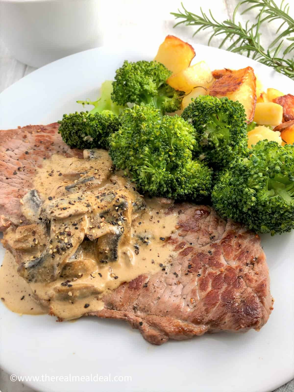rose veal escalopes on plate with mushroom sauce and broccoli and roasted potatoes
