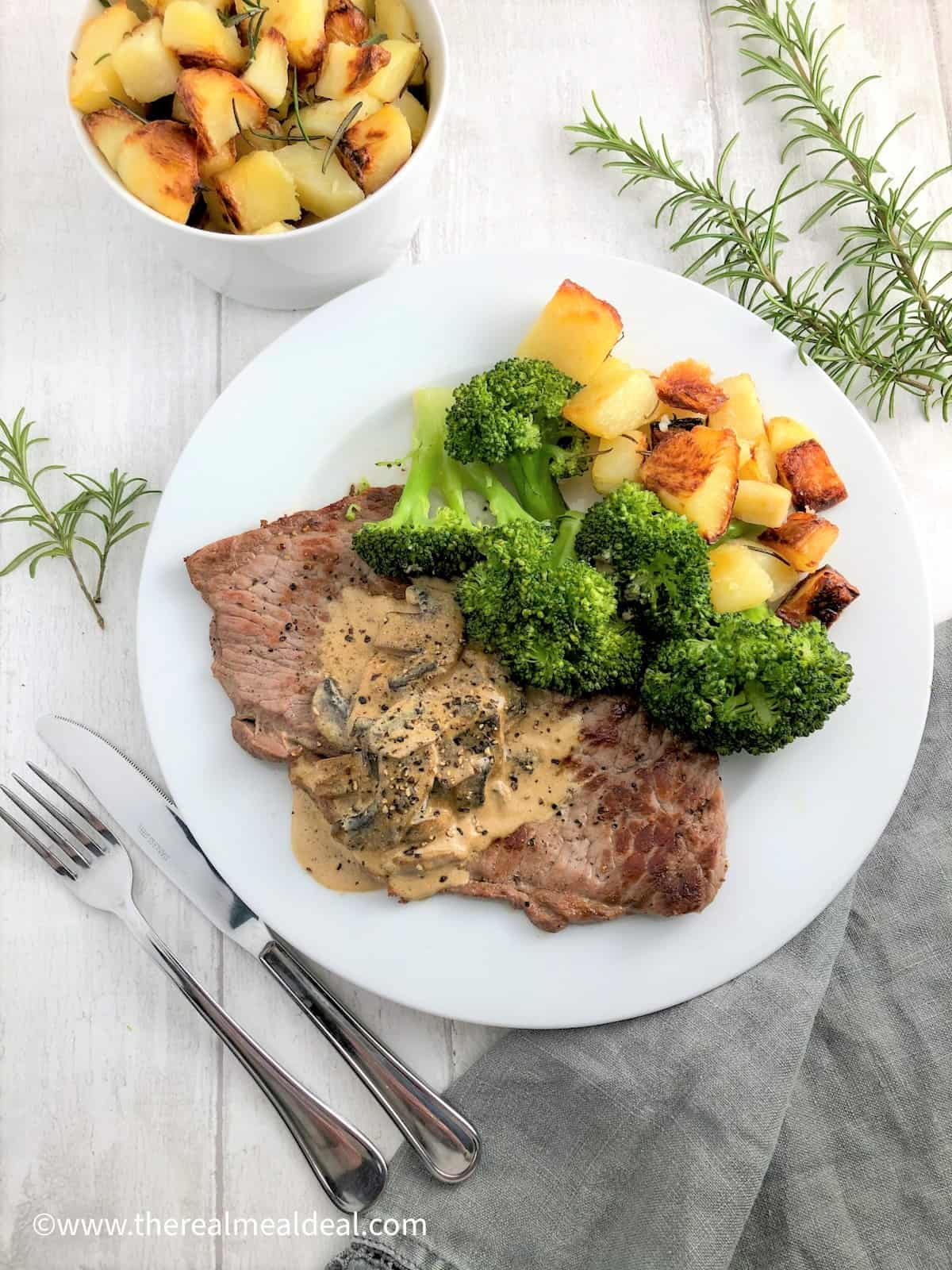 Rose veal escalope with creamy mushroom sauce and rosemary roasted potatoes and broccoli on plate with roasted potatoes in bowl to side with fresh rosemary leaves