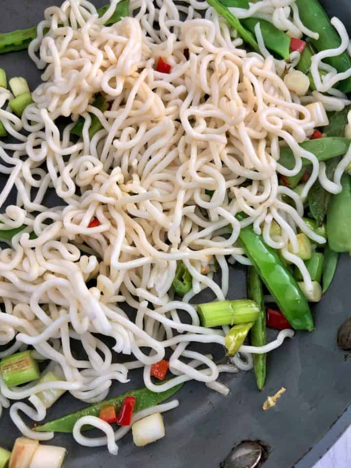 noodles added to spring onions red chilli and mangetout in pan
