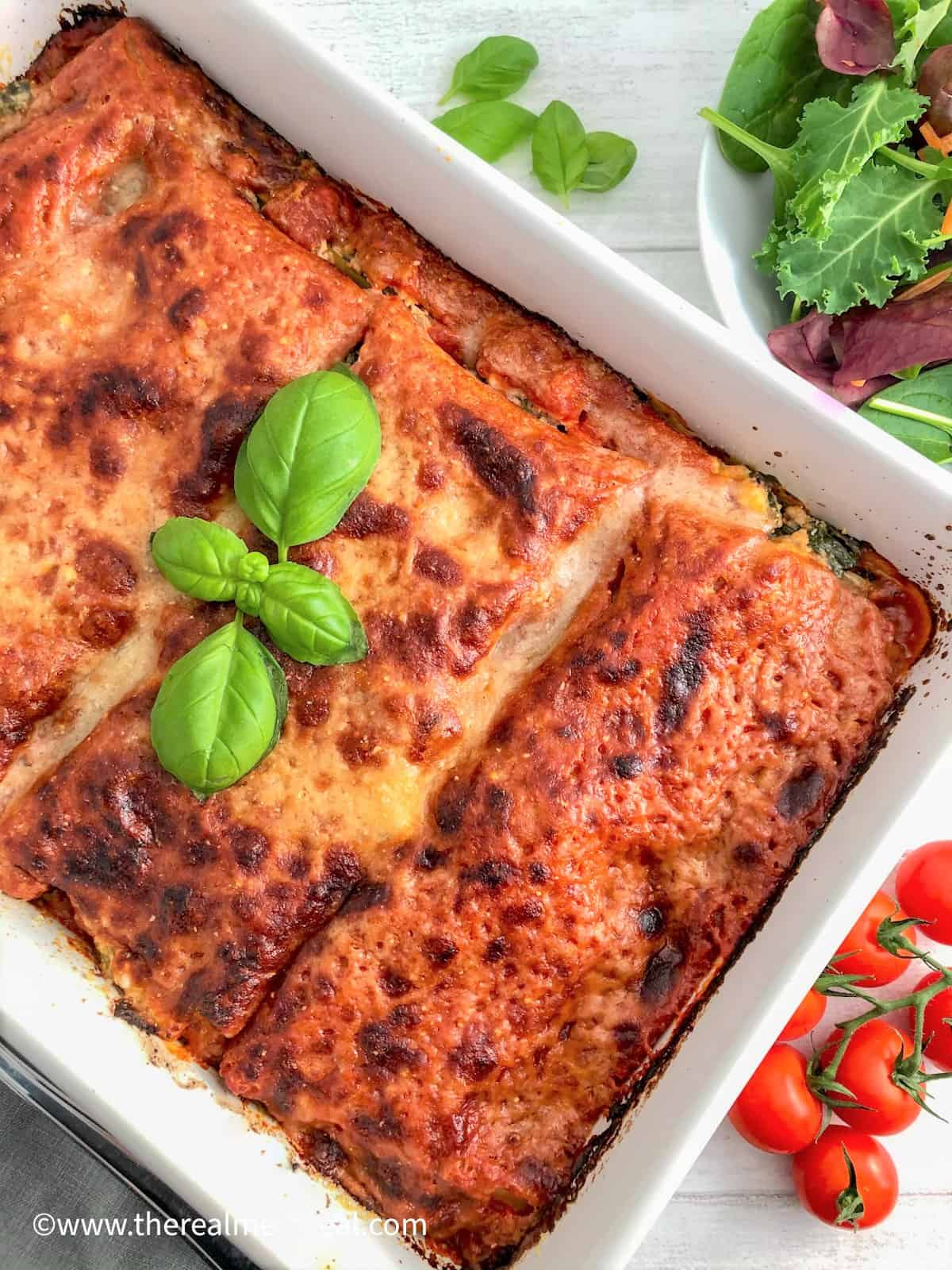 Spinach and Ricotta Lasagne baked in dish with cherry tomatoes and side salad