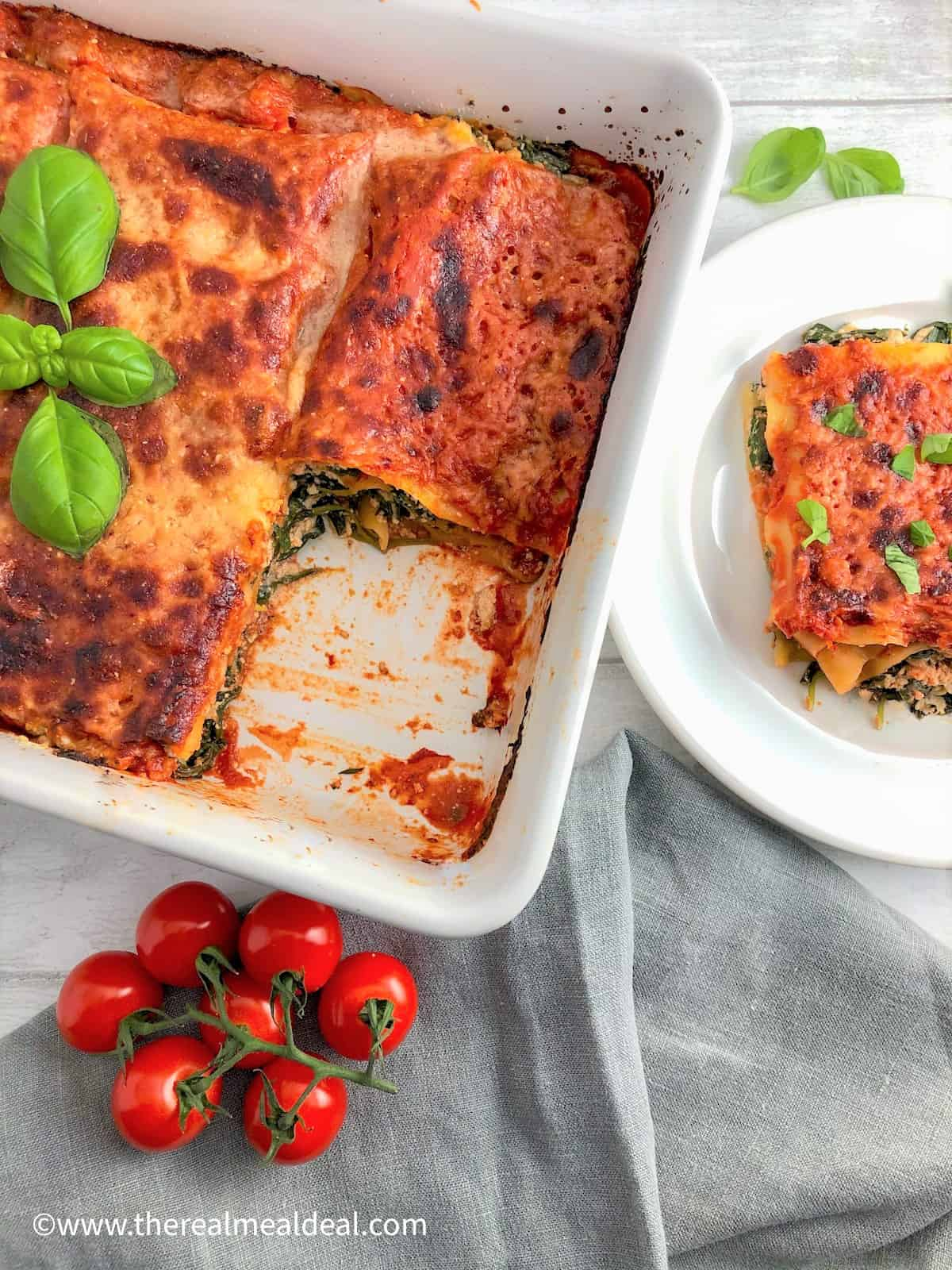 spinach and ricotta lasagne in dish with portion removed and plated to one side