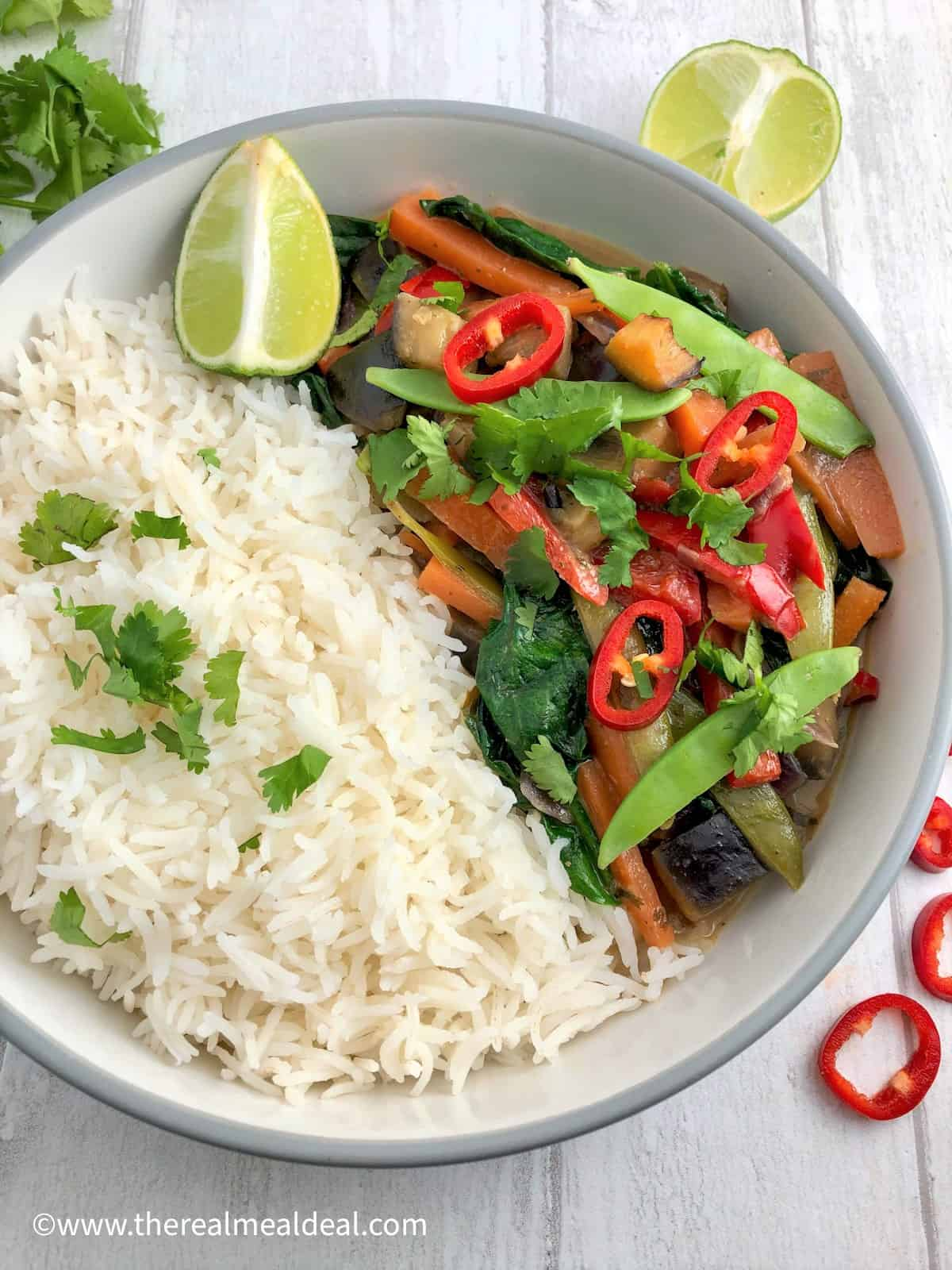 thai vegetable curry in bowl with white rice topped fresh coriander leaves and red chilli slice lime