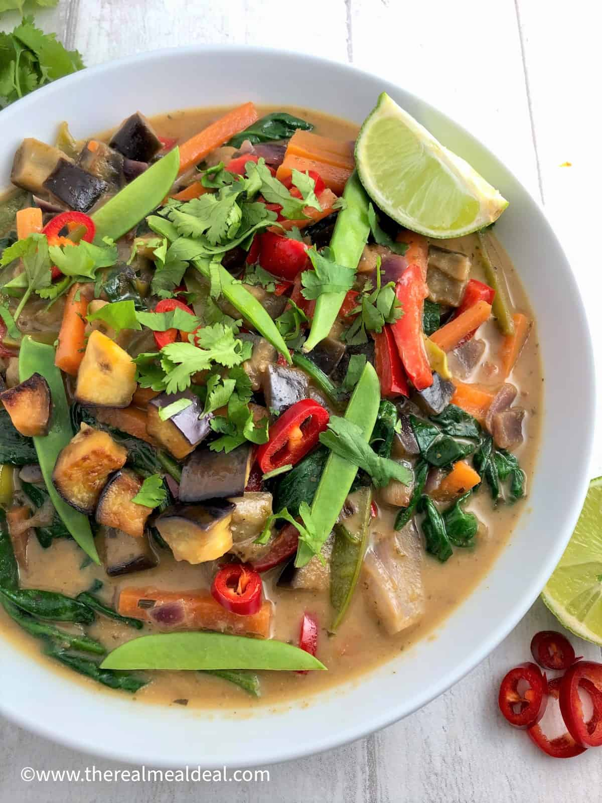 Thai vegetable green curry in bowl topped with fresh coriander red chilli and slice lime