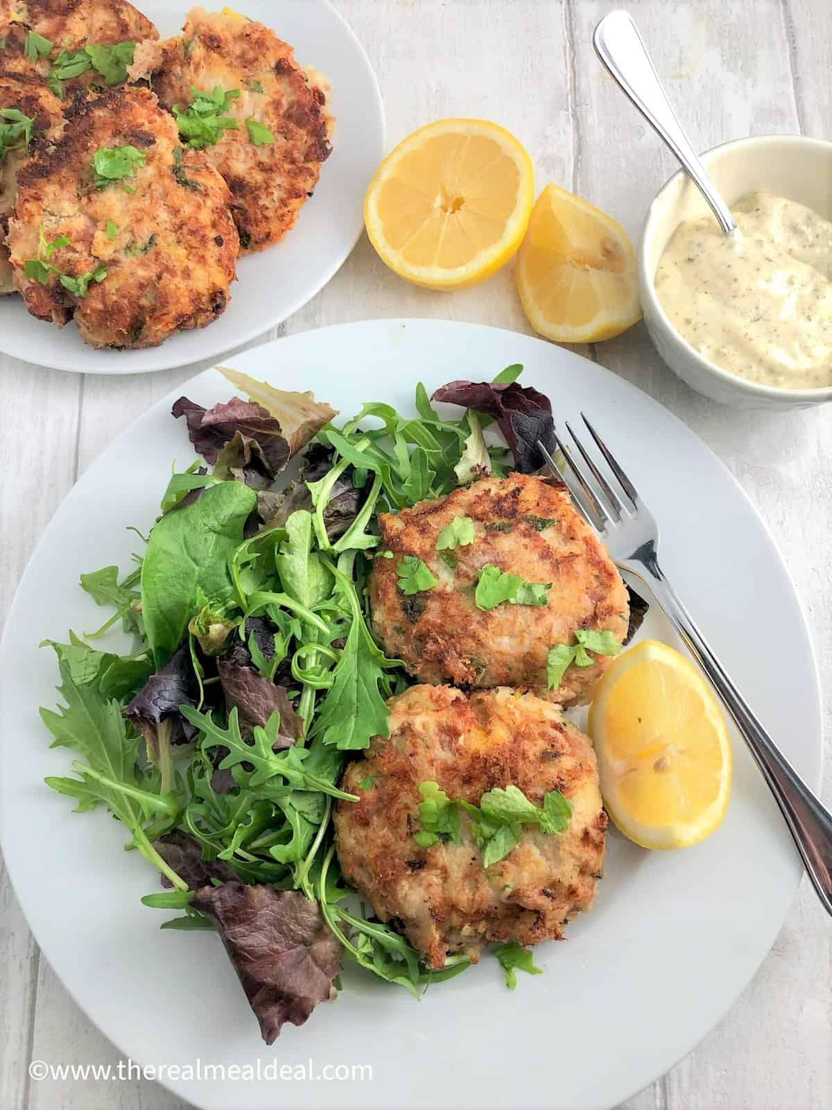 tuna fishcakes on plate with green salad and lemon half plate fishcakes lemon halves tartare sauce in background