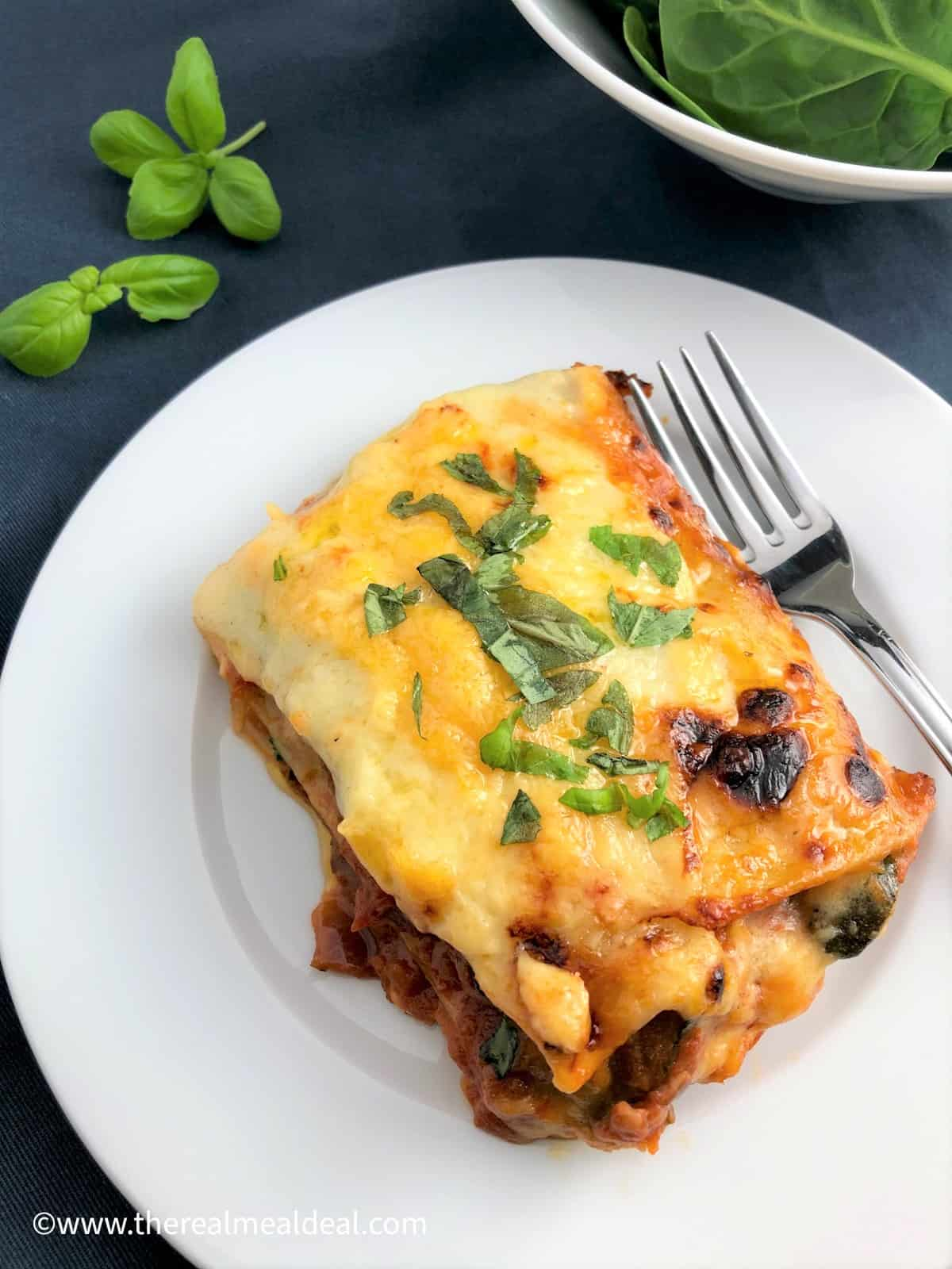 portion vegetable lasagne on plate with fork on blue cloth fresh basil leaves and spinach to side