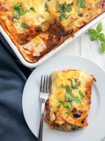 vegetable lasagne in tray with portion plated to side topped with fresh basil leaves