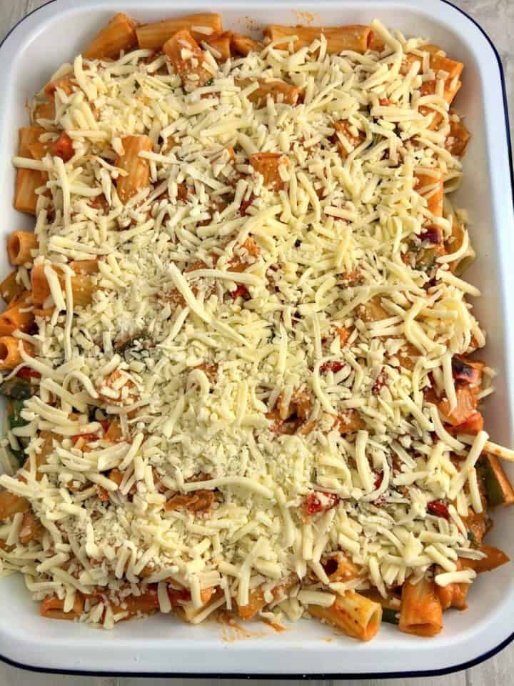 pasta bake in oven proof dish topped with grated mozarella cheese