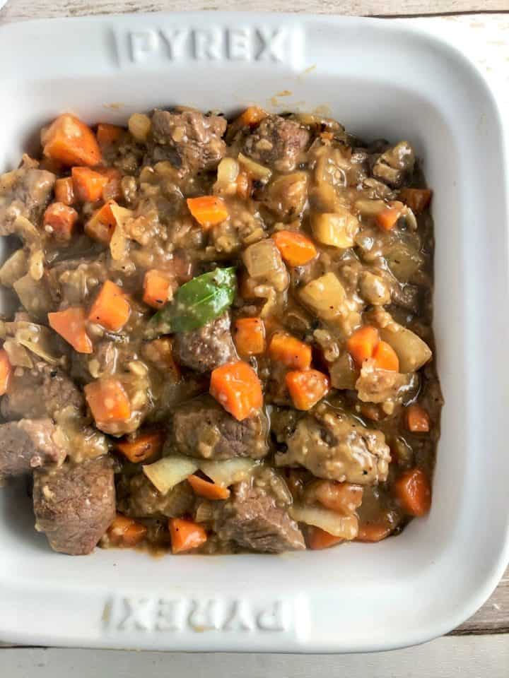 beef onions carrots and stock in casserole dish